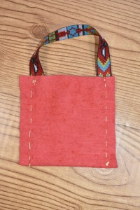 This image shows the final product after a child made her first purse or satchel from felt and a ribbon.