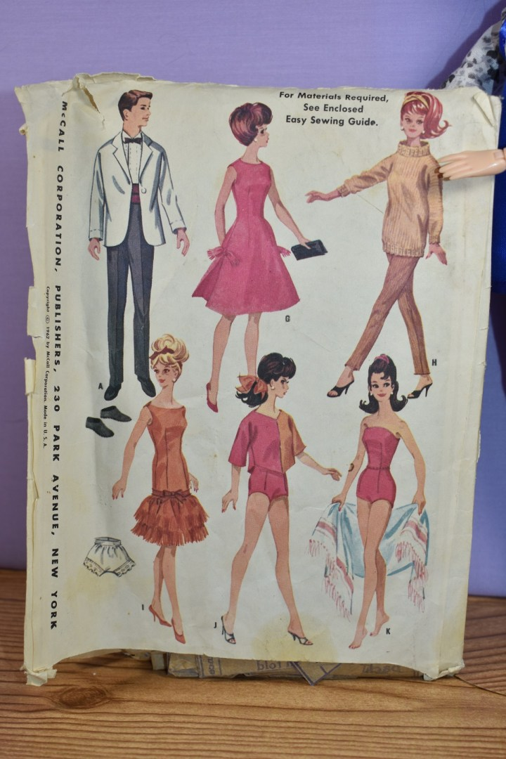 The image shows a close up of the back side of McCall's craft pattern #6420 which was printed in 1962. There are six outfits pictured here, including a white jacket tuxedo with cummerbund, pants, and felt shoes for Ken, a fairly simple dress with clutch purse for Barbie, a pair of ankle pants with a sweater that has a collar for Barbie, an evening gown with a short skirt that has a ruffle for Barbie (and includes a pair of underpants), a 1960's style swimsuit for Barbie, and a swimsuit cover-up for Barbie. To learn more about this pattern, please go to ChellyWood.com and use the search tool for Pattern #6420