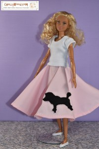 The image shows a Made to Move Barbie modeling a handmade 1950's style poodle skirt in pink with a black silhouetted poodle sewn to the fabric. She also wears a handmade T-shirt and flat white shoes. This Barbie has a dark complexion with blond curly hair. The website in the background is ChellyWood.com, a site that offers free printable sewing patterns for making doll clothes to fit dolls of many shapes and all different sizes.