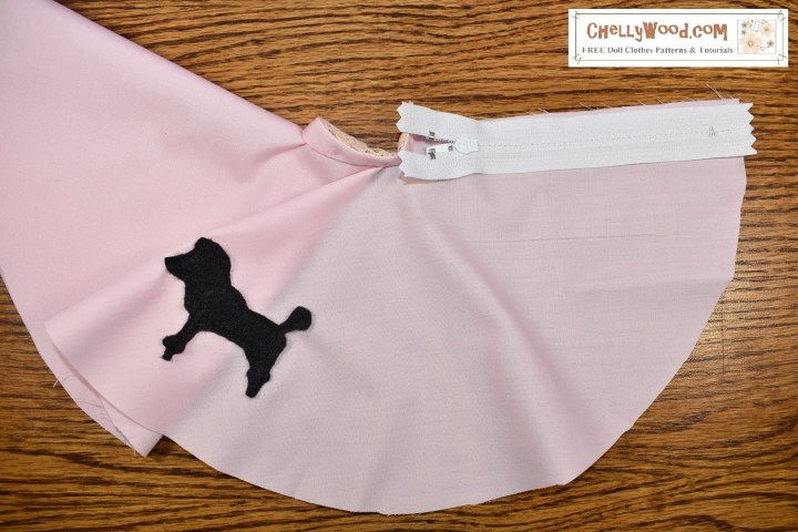 The image shows a pink circle skirt under construction with a zipper sewn to one half of its black closure area.