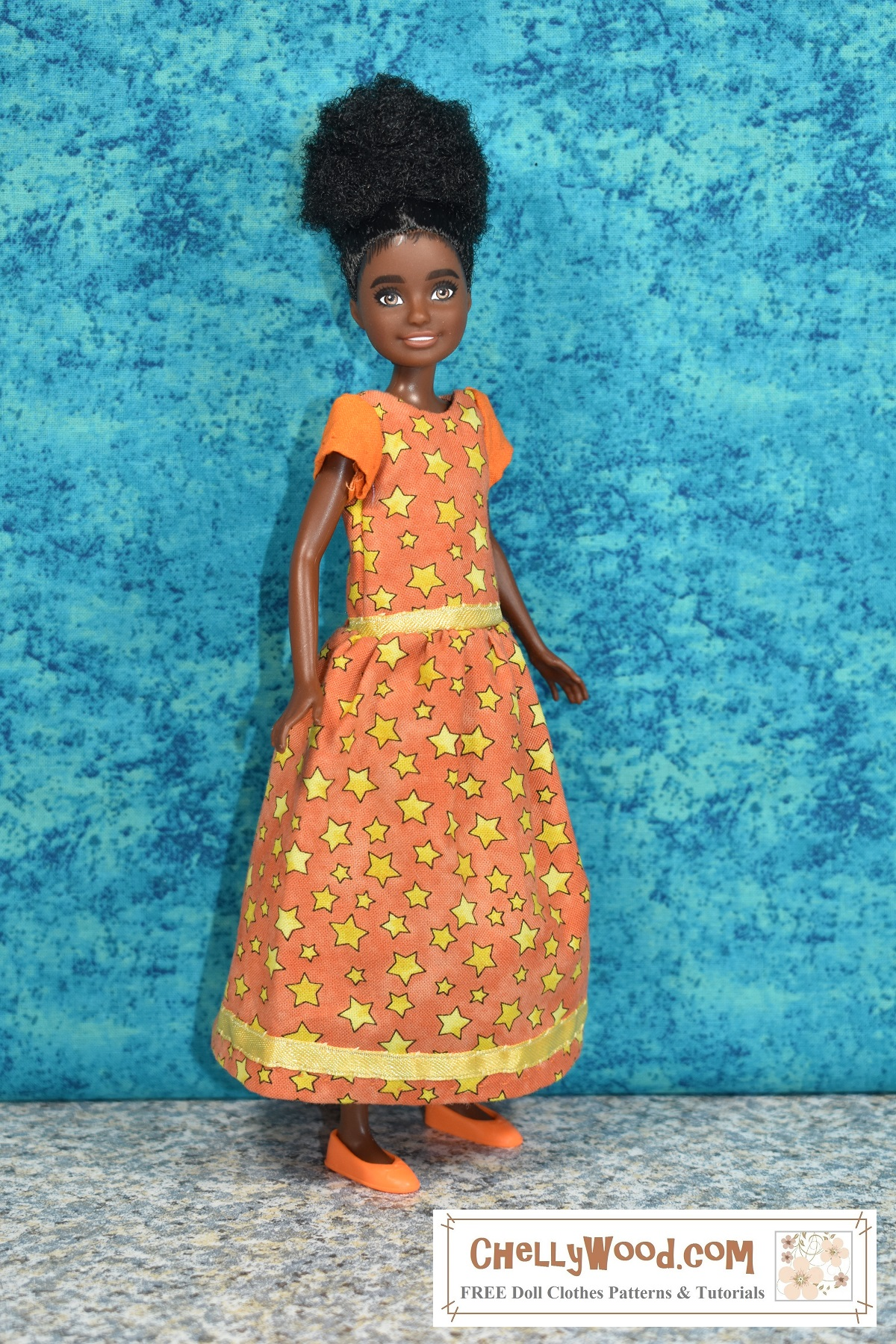 """The image shows a """"Team Stacie"""" friend-of-Stacie 9"""" doll modeling a handmade doll in a pretty bright orange color. The primary fabric is decorated with yellow stars of many sizes. The dress has a yellow ribbon trim along the bottom of the skirt and at the waist. The sleeves are made of solid orange fabric, unlike the rest of the dress, which is patterned with yellow stars on an orange background. The doll's bright orange flats match the color of her dress. The doll's plastic skin is milk-chocolate-colored, and her hair is naturally kinky and rich brown-to-black. The doll's face is framed in wispy black painted-or curls which match the color of her slightly raised eyebrows. She smiles at the camera. In the corner of the image is a logo which reads """"ChellyWood.com: free doll clothes patterns and tutorials."""" To make this dress, click on the link in the caption; it will take you to a page where you can find free printable PDF sewing patterns and tutorial videos to help you make this lovely harvest or Halloween party dress for your 8-inch or 9-inch (20 to 22 cm) dolls."""