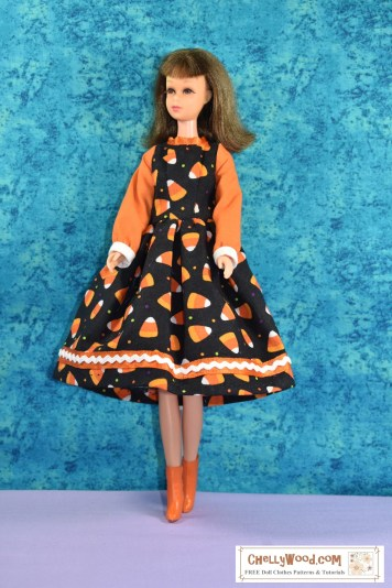The image shows a vintage Francie doll with bangs wearing a handmade Halloween party dress. The dress uses a patterned fabric decorated with tiny candy corns for the bodice front and back plus the skirt. The sleeves are made of solid orange fabric. The skirt is trimmed in orange ribbon with a layer of rickrack over the top. The sleeves have a bias tape cuff at the doll's hands. The collar is made of an orange ribbon. If you'd like to download the free printable PDF sewing pattern for making this Halloween party dress to fit your vintage Francie doll (also fits other dolls too), please click on the link in the caption.