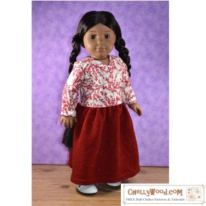 """The image shows an 18-inch """"Kaya"""" American Girl doll, wearing handmade doll clothes that were sewn using the free printable PDF sewing patterns found at ChellyWood.com. These free 18 inch doll clothes sewing patterns included a pattern for a long holiday skirt made of glittery red fabric and a long-sleeved V-neck blouse made of winter berry red and white cotton fabric. The doll's long braided hair goes all the way down her back, looking especially elegant with her long skirt. She wears white Mary Jane """"patent leather"""" style shoes. The overlaying watermark tells you to go to ChellyWood.com for your free printable PDF sewing pattern for making doll clothes for dolls of many shapes and all different sizes."""
