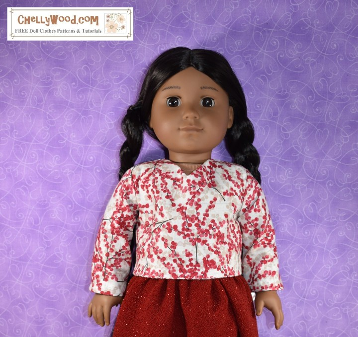 Here we see an 18 inch American Girl doll wearing a handmade V-neck shirt with long sleeves. The shirt is made of white cotton fabric with a winter berry print in red and grey. If you'd like the free printable PDF sewing patterns for making this shirt, please go to ChellyWood.com and search for 18 inch doll clothes (followed by) American Girl doll clothes patterns.