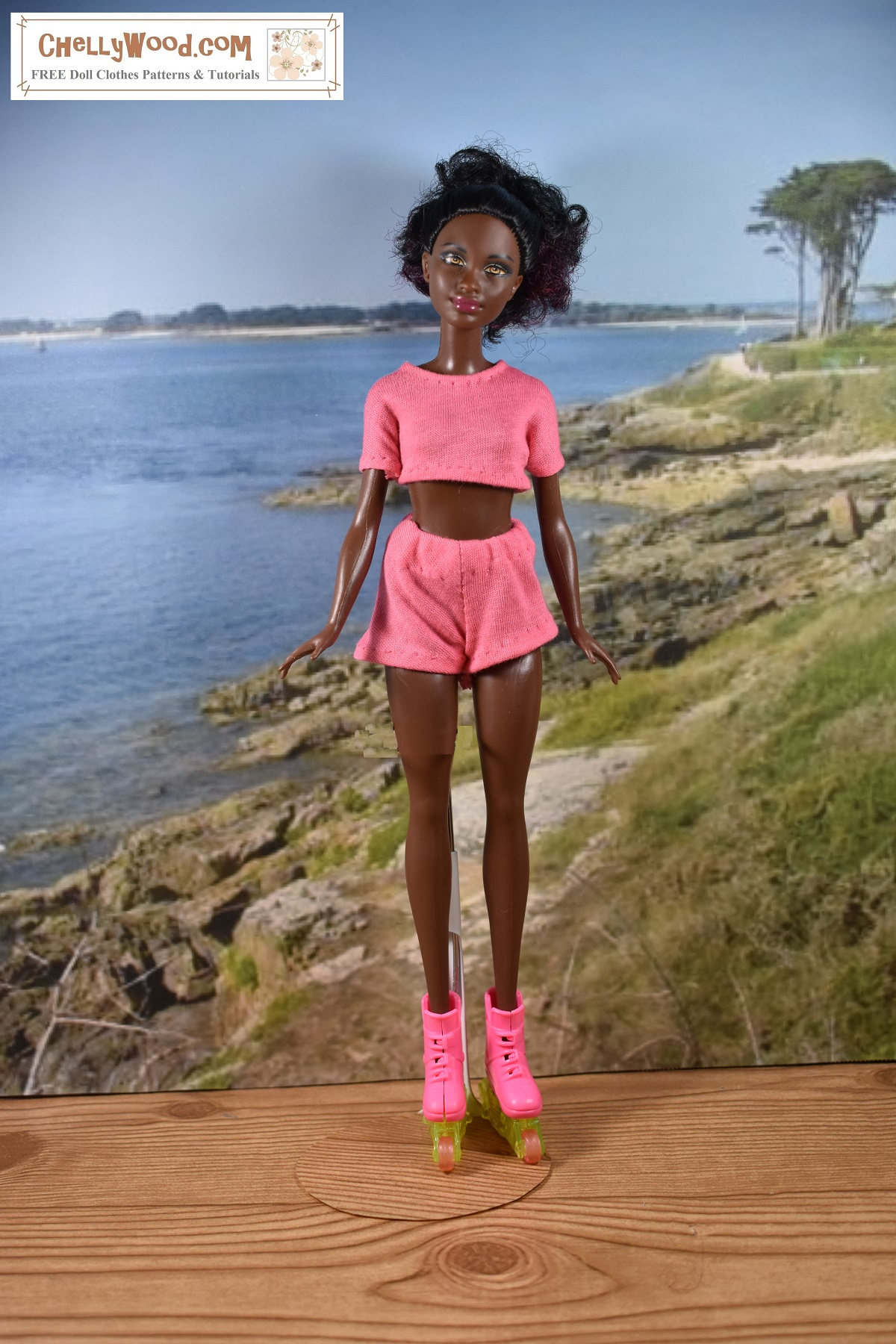 This image shows a Petite Barbie from Mattel wearing handmade doll clothes which include a crop top T-shirt and elastic waist sporty shorts. The free printable PDF sewing patterns for making this outfit for your Petite Barbie (or dolls that are similar in size) can be found at ChellyWood.com under the 10-inch doll clothes pattern gallery.