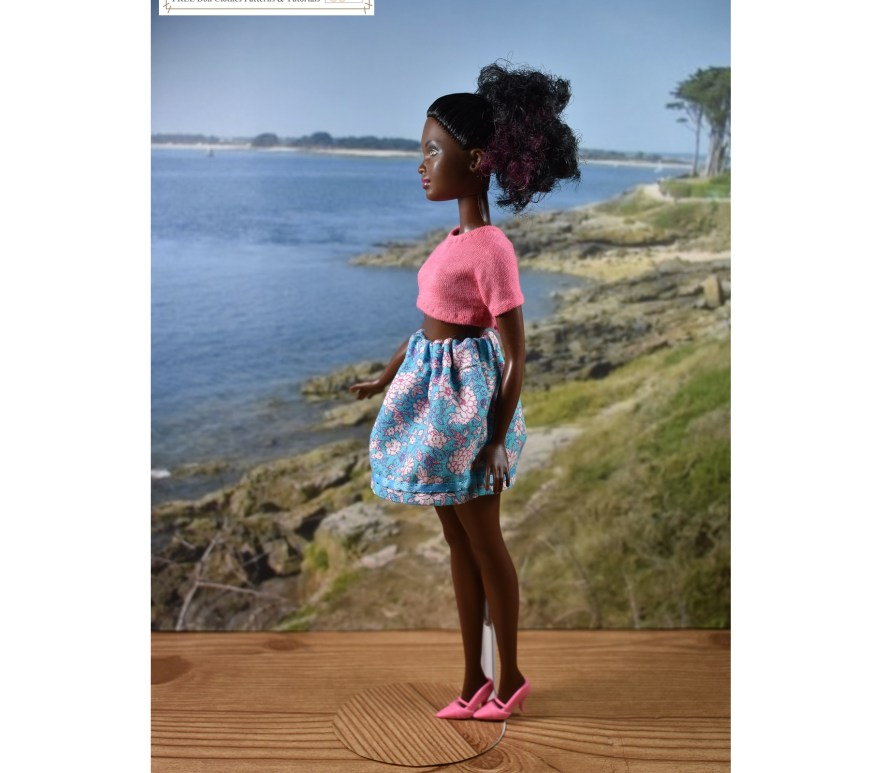 This image shows a 10 inch Petite Barbie from Mattel modeling handmade doll clothes which include a skirt with an elastic waist and a crop top tee shirt. If you'd like to download the free printable PDF sewing patterns for making this outfit, please go to ChellyWood.com and navigate to the 10-inch doll clothes pattern gallery, so the free printable patterns will fit your 10 inch Petite Barbie or a similar sized doll.
