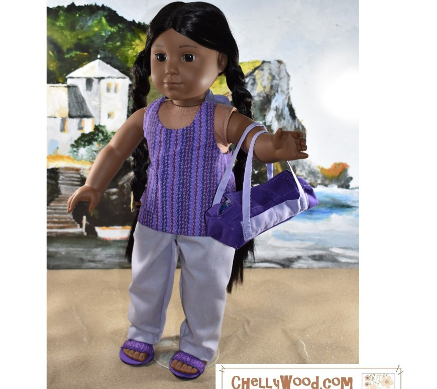 The image shows an American Girl Kaya doll wearing handmade doll clothes and carrying a handmade duffle bag / overnight bag / gym bag. She's also wearing handmade sandals. Her outfit consists of an easy to sew halter top and elastic waist lavender colored pants / trousers. She's standing on the sand at a beach with the ocean and a fancy beach house that resembles a castle behind her. The watermark tells you where you can download the free printable PDF sewing pattern for making the whole doll clothes ensemble: ChellyWood.com