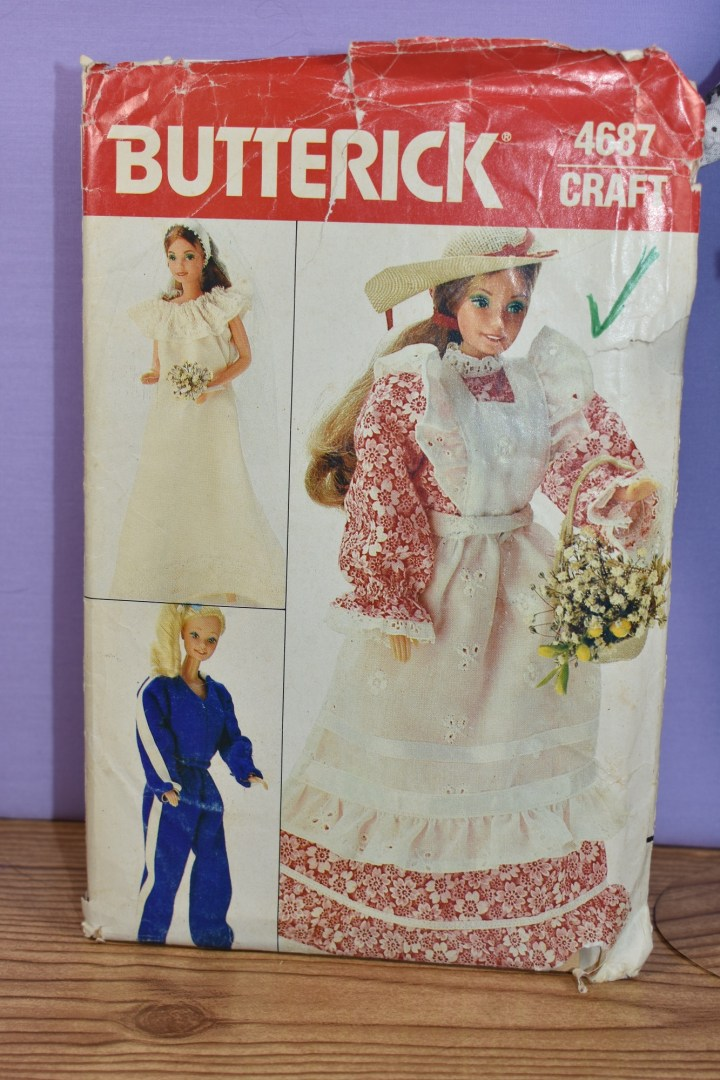 This image shows a commercial pattern: Butterick Craft Pattern #4687, which offers patterns for making a night gown, a sweat suit, and a long pioneer-style dress with a pinafore. All patterns are designed to fit 11.5 inch dolls like Mattel's Barbie dolls.