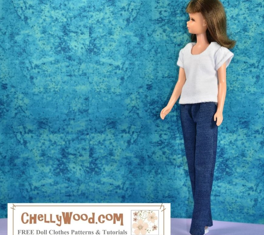 "The image shows a vintage Francie doll from Mattel, wearing white flat shoes, a pair of stretch denim blue jeans (called ""dungarees"" in some countries), and a short-sleeved, scoop neck T-shirt (sometimes spelled tee shirt) in solid white. She stands beore a paint-splattered blue background. The watermark tells you where you can go online to download the free printable PDF sewing patterns for making this whole outfit: ChellyWood.com (which also offers free tutorial videos showing how to make these jeans and the T-shirt as well). Click on the link in the caption to navigate to the page where you can find the free printable PDF sewing patterns for all of these doll clothes that fit Francie and similar-sized dolls."