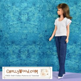 """The image shows a vintage Francie doll from Mattel, wearing white flat shoes, a pair of stretch denim blue jeans (called """"dungarees"""" in some countries), and a short-sleeved, scoop neck T-shirt (sometimes spelled tee shirt) in solid white. She stands beore a paint-splattered blue background. The watermark tells you where you can go online to download the free printable PDF sewing patterns for making this whole outfit: ChellyWood.com (which also offers free tutorial videos showing how to make these jeans and the T-shirt as well). Click on the link in the caption to navigate to the page where you can find the free printable PDF sewing patterns for all of these doll clothes that fit Francie and similar-sized dolls."""