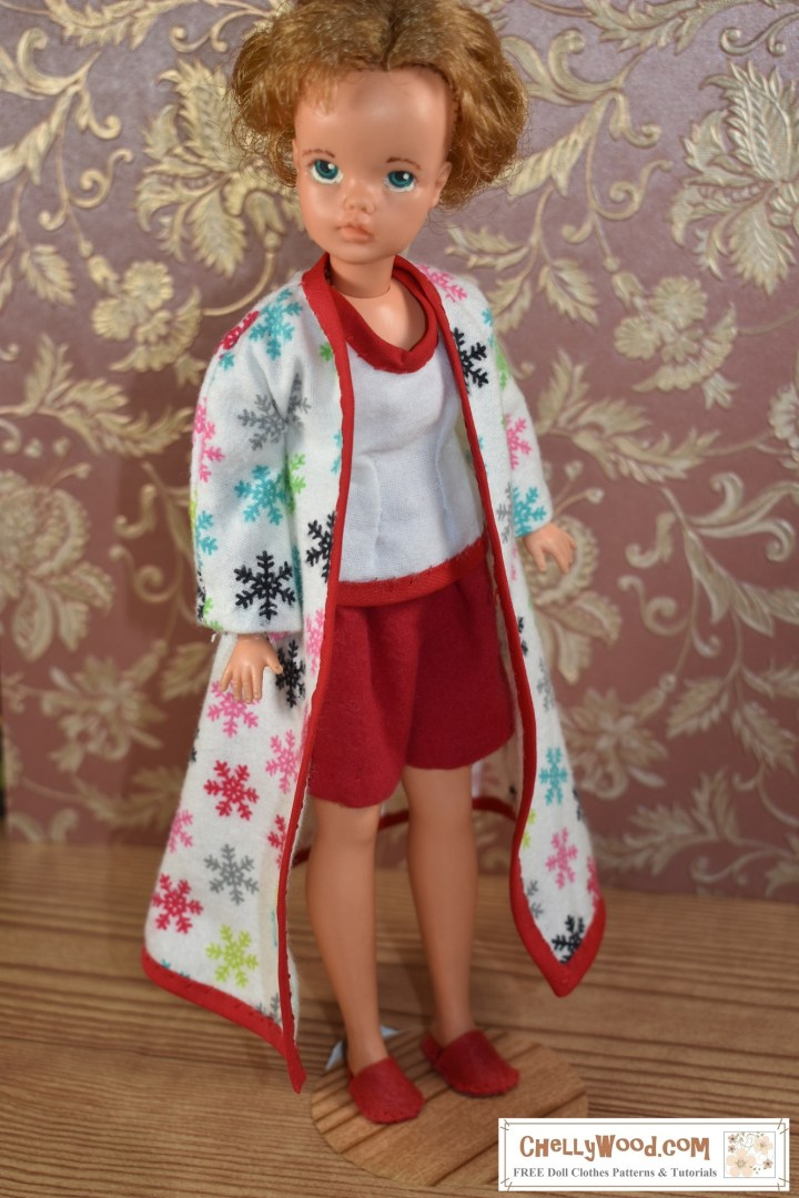 "If you'd like to download the free PDF sewing patterns and watch the sewing tutorials for making this outfit for your 12 inch fashion dolls, please click on the link in the caption. This image shows a vintage Tammy doll from Ideal Toy Company wearing handmade pajama shorts, a handmade pajama top, a pair of handmade felt slippers, and a handmade flannel bathrobe. The entire ensemble is decorated in the key colors of red and white. Tammy stands at an angle to the camera, and her bathrobe has fallen open to show off her flannel shorts and flannel sleeveless pajama top. It looks like her makeup has been removed for that honest ""morning look"" after sleeping in."