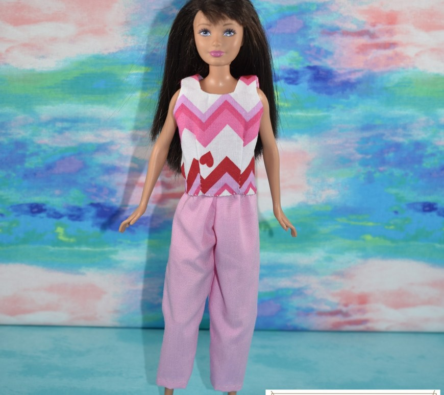 The doll faces the camera straight-on in this photo. The image shows Skipper modeling a pair of pink long capri pants or ankle pants with a sleeveless shirt of cotton, made with a fabric that has zig-zagging stripes in pink, red, and white plus tiny red hearts dotted across the zig-zag pattern. The watermark reminds you to go to ChellyWood.com for free printable PDF sewing patterns.