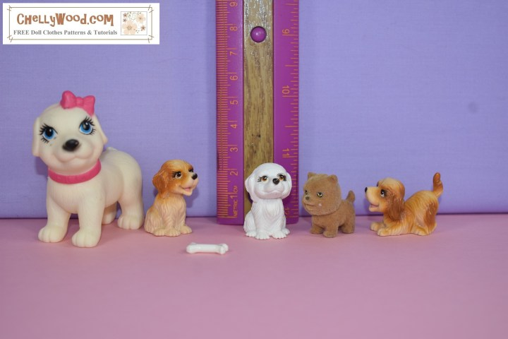 The image shows five tiny dogs and one miniature dog bone. the dogs are next to a ruler leaned up against the backdrop. It shows that the dogs range in size from just under one inch to 5 cm or almost 2 inches tall.