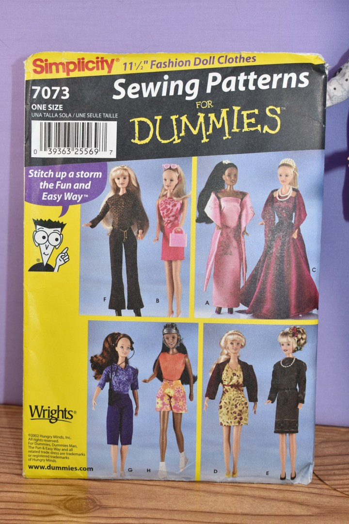 "The image shows a closer view of Simplicity fashion doll sewing pattern 7073 ""for dummies"" which includes pants, shorts, skirts, blouses, and a long gown."