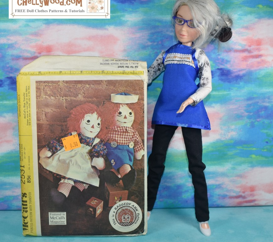 "The image shows the Chelly Wood doll (a re-designed Spin Master Liv doll with grey hair and wrinkles) holding up a Raggedy Ann and Andy plush doll pattern from the year 1970. It's McCall's craft pattern 2531, and it displays the classic Raggedy Ann and Andy with red yarn hair and Andy wears a sailor cap with a red gingham shirt while Raggedy Ann wears a dress with pinafore and bloomers. To learn about this pattern and what it means to various sewists online, go to ChellyWood.com to join the hashtag ""sewing chat"" along with Chelly's followers."