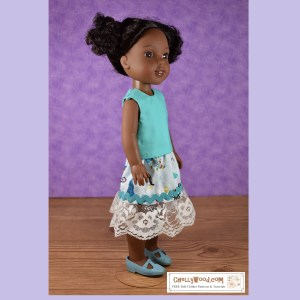 The image shows an African American Wellie Wisher doll wearing handmade clothes that include a sleeveless shirt and a mermaid-print skirt with rickrack trim and lace at the bottom of the skirt. The shirt has a round-neck style and is made of turquoise blue cotton. The skirt is sea blue with multi-colored fish and mermaids printed on it, and its rickrack trim is turquoise in color to nicely match the shirt this doll is wearing.
