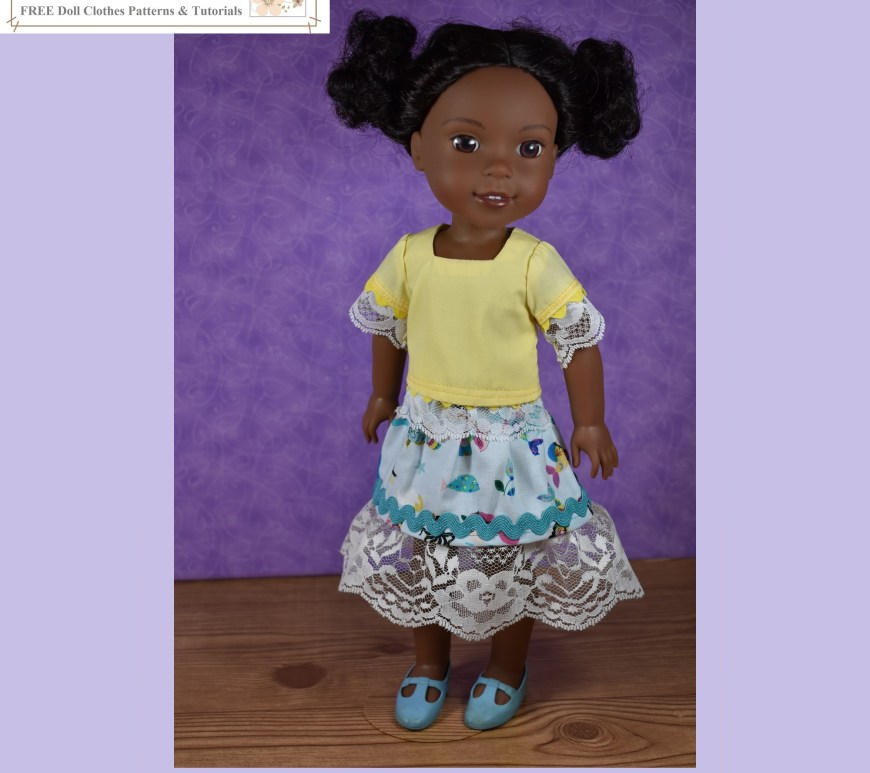 The image shows an African American Wellie Wisher doll wearing handmade clothes that include a short-sleeved shirt with rickrack and lace trim at the sleeves and a mermaid-print skirt with rickrack trim and lace at the bottom of the skirt. The shirt has a square-neck style and is made of creamy yellow cotton. The skirt is sea blue with multi-colored fish and mermaids printed on it (including one with yellow hair), and its rickrack trim is turquoise in color.