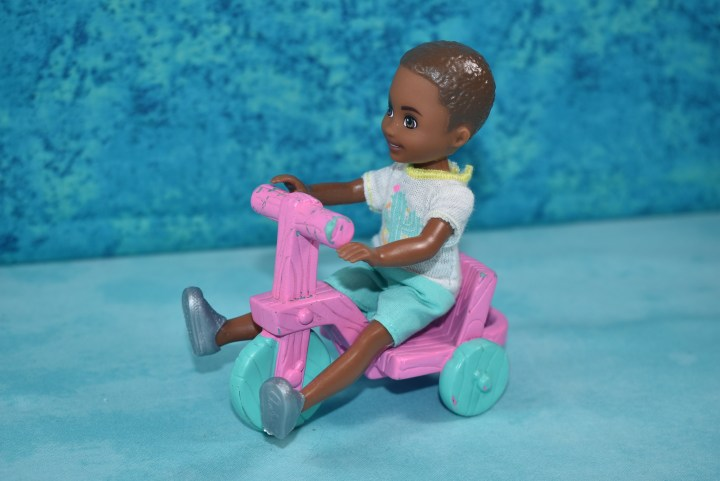 The Chelsea and Friends boy doll sits with his legs spread apart on the scooter and his hands touching the handlebars of the scooter.