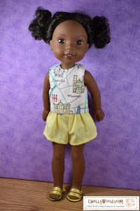 The image shows a Wellie Wisher in a reversible sleeveless shirt and a pair of elastic waist shorts. She also wears handmade sandals. Would you like to make these doll clothes for your Wellie Wisher doll (or a similar-sized doll)? Click on the link in the caption and it will redirect you to the page where these free printable doll clothes patterns can be found.