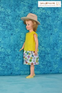 In this image, we see a vintage Pepper doll (in this photo the doll faces to her right) wearing a handmade floral multicolored cotton skirt and a handmade yellow felt sleeveless shirt. The doll's cheeks are pink, and her hair curls in front of her tiny ears.