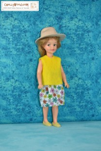 """In this image, we see a vintage Pepper doll (the vintage Tammy doll's little sister from the Ideal Toy Corporation) wearing a handmade floral cotton skirt and a handmade yellow felt sleeveless shirt. She also sports a pair of yellow loafers and a tan plastic """"Indiana Jones-style"""" safari hat. If you would like to download the free printable PDF sewing patterns for making these doll clothes for your Pepper doll, please click on the link in the caption."""
