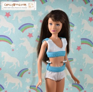 Here we see a Mattel Skipper doll looking to her right. She is posed with arms slightly extended. She wears a handmade set of under garments or possibly a swimsuit. The bra is a sporty sports bra style garment with white cotton jersey fabric for the top half of the sports bra and blue elastic for the bottom half of the sports bra. The straps are made of the same turquoise blue elastic as the bottom half of the sports bra. The underpants (or swimsuit bottoms) are made of white cotton jersey fabric with the same turquoise blue elastic waistband that we see in the straps and bottom half of the sports bra. The underpants elastic just barely covers the doll's belly button. These would be considered briefs in terms of under clothing styles. For the free printable PDF sewing patterns and free tutorials to make these 10 inch doll underwear doll clothes items, please go to ChellyWood.com.