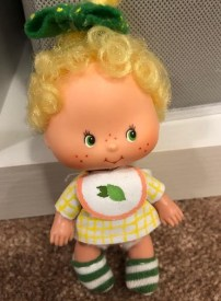 The image shows a tiny Strawberry Shortcake baby doll (probably a Lemon Meringue doll) wearing a yellow plaid shirt with a tiny bib and teeny-tiny green and white striped socks. These doll clothes were designed and hand sewn by Sheri-Lyn S.