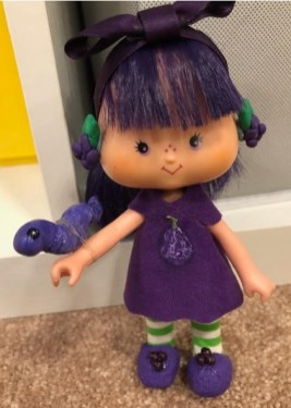 The image shows a purple-haired Strawberry Shortcake doll wearing a handmade purple dress, shoes, and a purple ribbon in her hair. These doll clothes were designed and sewn by Sheri-Lyn S.
