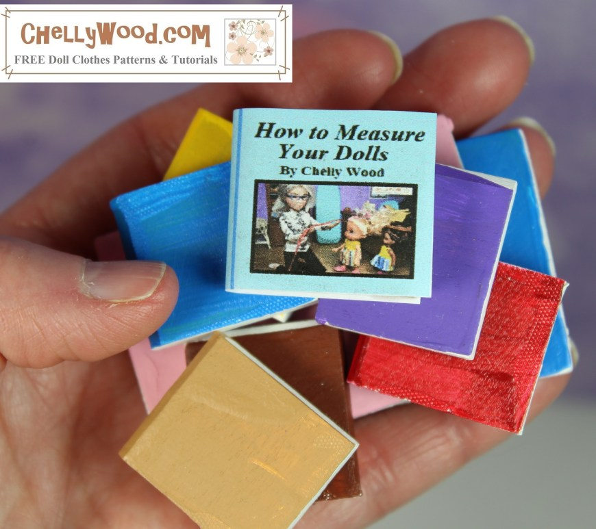 "The image shows the close-up of a human hand holding ten different tiny books. The one on top is particularly small and has a paper dustjacket. The title of the book reads as follows: ""How to measure your dolls, by Chelly Wood."" All other books appear to be painted with tiny white pages and covers of various colors including tan, brown, red, purple, bright blue, yellow, and pink. The watermark reminds you to visit ChellyWood.com for free doll clothes patterns and tutorials."