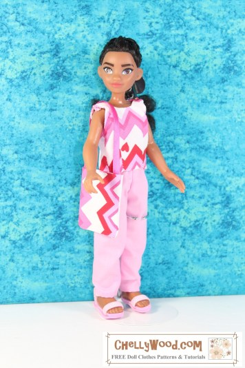 The image shows a 9 inch or 10 inch Moana doll (from the Disney Princess collection) modeling handmade doll clothes designed by Chelly Wood of ChellyWood.com. These free printable PDF sewing patterns are available at the link found in the caption. The outfit includes a sleeveless summer shirt made of cotton and a pair of cotton ankle pants. The outfit also includes a purse. The free patterns for this outfit use the Creative Commons Attribution mark, which means you're free to download and print the patterns, and you can sell the products you make with them; however, please tell people where your patterns come from to help promote and support this website.