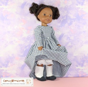 """The image shows a Wellie Wisher doll modeling a pair of Victorian boots with Edwardian-style """"spats"""" and tiny black buttons that appear to button them up. She's lifting the skirt of her gingham dress slightly, so the very bottom of her lace-edged bloomers are showing above the boots. The watermark reminds us that this image comes from ChellyWood.com, where you can find """"free doll clothes patterns and tutorials."""""""