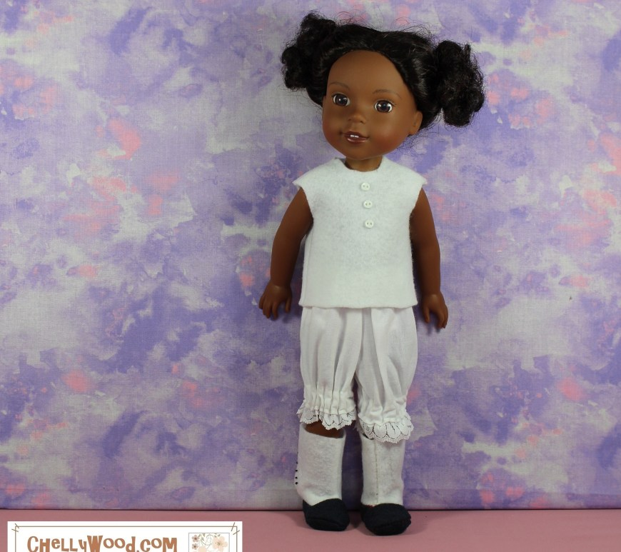 "This image shows a Wellie Wishers doll wearing a handmade undershirt made of felt, a pair of cotton bloomers with lace trim, and a pair of felt boots in either a Victorian style or an Edwardian-spats-style. Her underclothes are all white, and she stands with pigtailed hair in front of a mottled purple and pink background. Her boots have white ""spats"" (or they look like spats rather) over the top of navy blue shoes/boots. She stands on a dusty rose colored platform. If you would like to make this outfit, please go to ChellyWood.com to download the free printable sewing patterns and to watch the free tutorial videos showing you how to make this outfit."