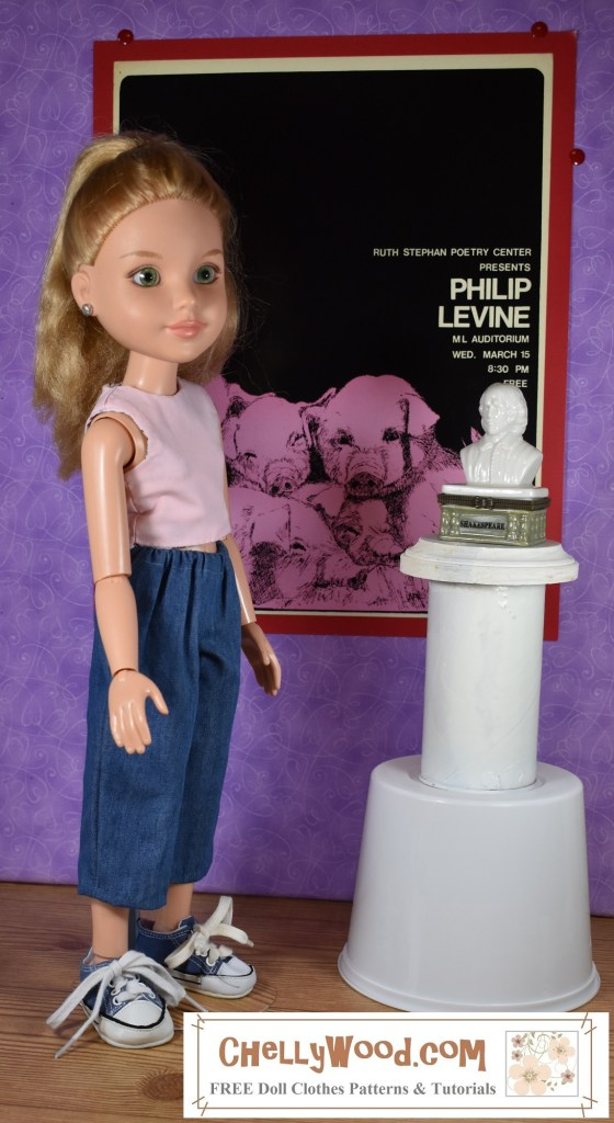 """The photograph shows a BFC Ink 18 inch doll standing in what appears to be a doll-sized museum. In front of the doll is a bust of Shakespeare. Beside the doll, hanging on the wall, is a strange poster of pink pigs all piled up with a black background behind them. The name """"Philip Levine"""" is displayed on the background, along with undecipherable words. The doll stands closer to the camera, and we can see that she's wearing handmade doll clothes. Her shirt is a pink reversible crop top tank top, and her pants are denim capris with an elastic waist. She also wears denim tennis shoes. The watermark says, """"ChellyWood.com : free doll clothes patterns and tutorials."""""""