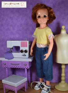 """The image shows a 1970's Ideal Crissy doll with red hair that grows. She wears a handmade boxy-looking square-necked crop top shirt with shoulder-length sleeves (the sleeves and bottom of the shirt are trimmed in lace) and a pair of elastic-waist denim capri pants. Beside the doll, on her right, is a sewing table, sewing machine, and bench seat where Crissy can sit to sew. Beside the Crissy doll on her left is a tan-colored sewing mannequin (sometimes referred to as a """"dress form"""" for sewing enthusiasts). The watermark on this image says """"ChellyWood.com : free doll clothes patterns and tutorials."""""""