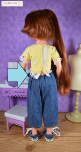 Here we see an Ideal Crissy doll. Her long hair is moved aside to expose the back closure area of her shirt. The shirt is being held closed somewhat precariously with a strip of Velcro, and the knob for retracting Crissy's hair is exposed a bit under the shirt.