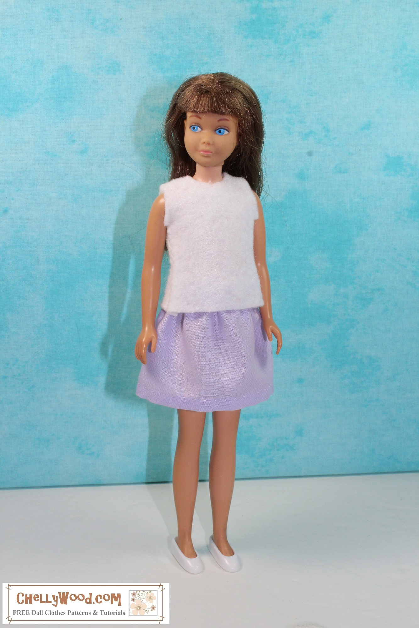 Here we see a vintage Skipper doll from Mattel wearing handmade doll clothes that include an easy-to-sew felt sleeveless summer shirt and an easy sew elastic waist skirt. The felt shirt is white along with the doll's plastic shoes. The skirt is lavender colored, and it is a very short skirt, with the hem just above the knee. She looks adorable with her blue eyes turned slightly to her right. She has dark bangs and long brown hair. She stands before a turquoise colored background. If you'd like to make these cute and easy to sew doll clothes for your vintage Skipper or a similar sized 9 inch doll, click on the link in the caption. It will take you to a page where the free printable PDF sewing patterns are accompanied by links to the tutorials for making both the shirt and the skirt.