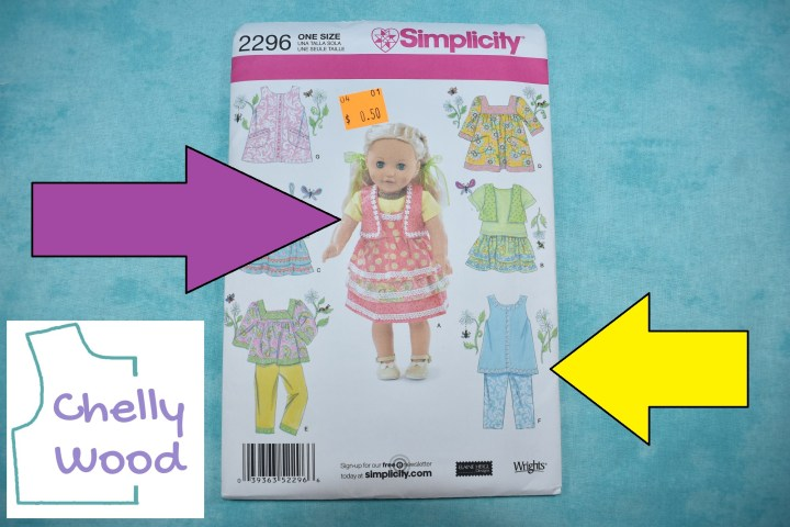 The photo shows the Simplicity 18 inch doll clothes pattern number 2296. In this close-up of the pattern, we see a purple arrow pointing at the main outfit on the front of the pattern packages. This central doll dress is made of a peach-colored fabric, and a vest is worn over the ribbon-embellished dress with multiple layers of skirts. There's also a yellow arrow pointing at one of the pants outfits. This outfit represented by an artist's drawing of a sleeveless shirt and simple pants in matching blue solid and blue floral fabrics. The photograph has been watermarked with the Chelly Wood dot com logo.