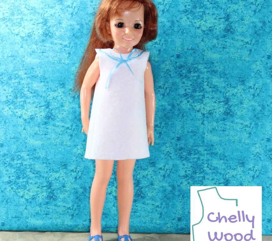 """This photograph shows a Crissy doll wearing a handmade shift dress and blue plastic shoes in front of a turquoise mottled background screen. The watermark reminds us to visit ChellyWood.com for the free pattern to make this """"sailor-style"""" shift dress with a round collar trimmed in ribbon. Click on the link in the caption to find the free printable PDF sewing pattern for this short shift dress."""