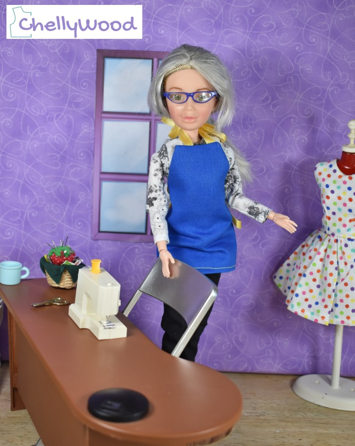 Here we see an image of Chelly Wood (the Liv doll that has been re-designed to look like the doll clothing designer, Chelly Wood) standing in her tiny sewing room, with her Galoob sewing machine on her right and her miniature dress form on her left. Behind her is the sewing room's window. On her sewing table (along with her tiny sewing machine) is a coffee cup and a sewing basket. The dress form sports a little party dress made of white cotton with multi-colored miniature polka dots. The watermark reminds us to go to ChellyWood.com for all the free printable PDF sewing patterns and tutorials we need for making a wardrobe of doll clothes to fit dolls of many shapes and all different sizes.