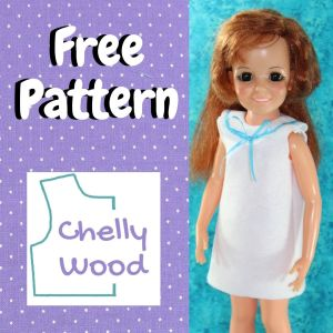 """Here we see a vintage Crissy doll with lovely ginger hair wearing a handmade felt sleeveless dress with a collar that is trimmed in blue ribbon tied in a bow at the front. The sleeveless dress is made of white felt. The image includes the words """"Free Pattern"""" and the name Chelly Wood on a logo of a bodice pattern."""