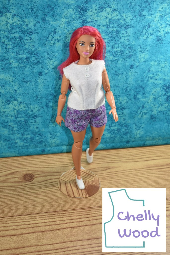 The image shows a Made-to-Move Curvy Barbie (from Mattel) wearing a handmade sleeveless felt shirt and cotton floral print shorts. Click on the link in the caption to navigate to the page where you can download a free printable PDF sewing pattern for making this shorts outfit for your Curvy Barbie or similar-sized dolls.