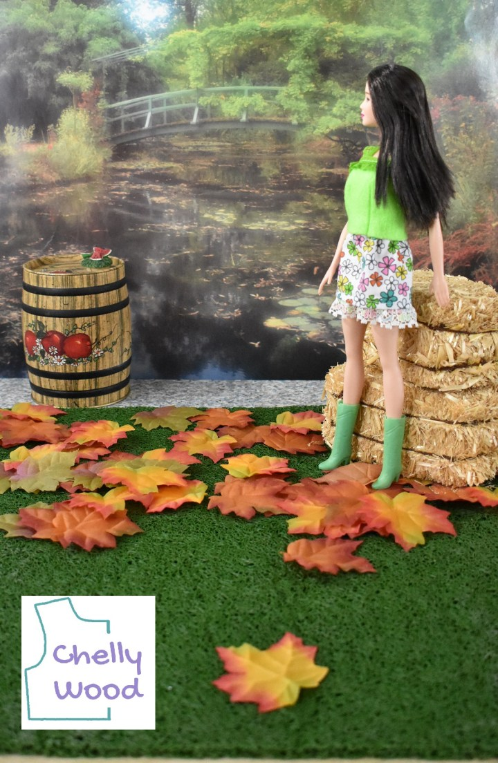 Here we see a Barbie modeling handmade doll clothes that include a felt summer top and a short floral mini skirt. She wears green plastic boots that match the color of her summer top. She leans against two bales of hay and looks to her right where there's a barrel of apples.