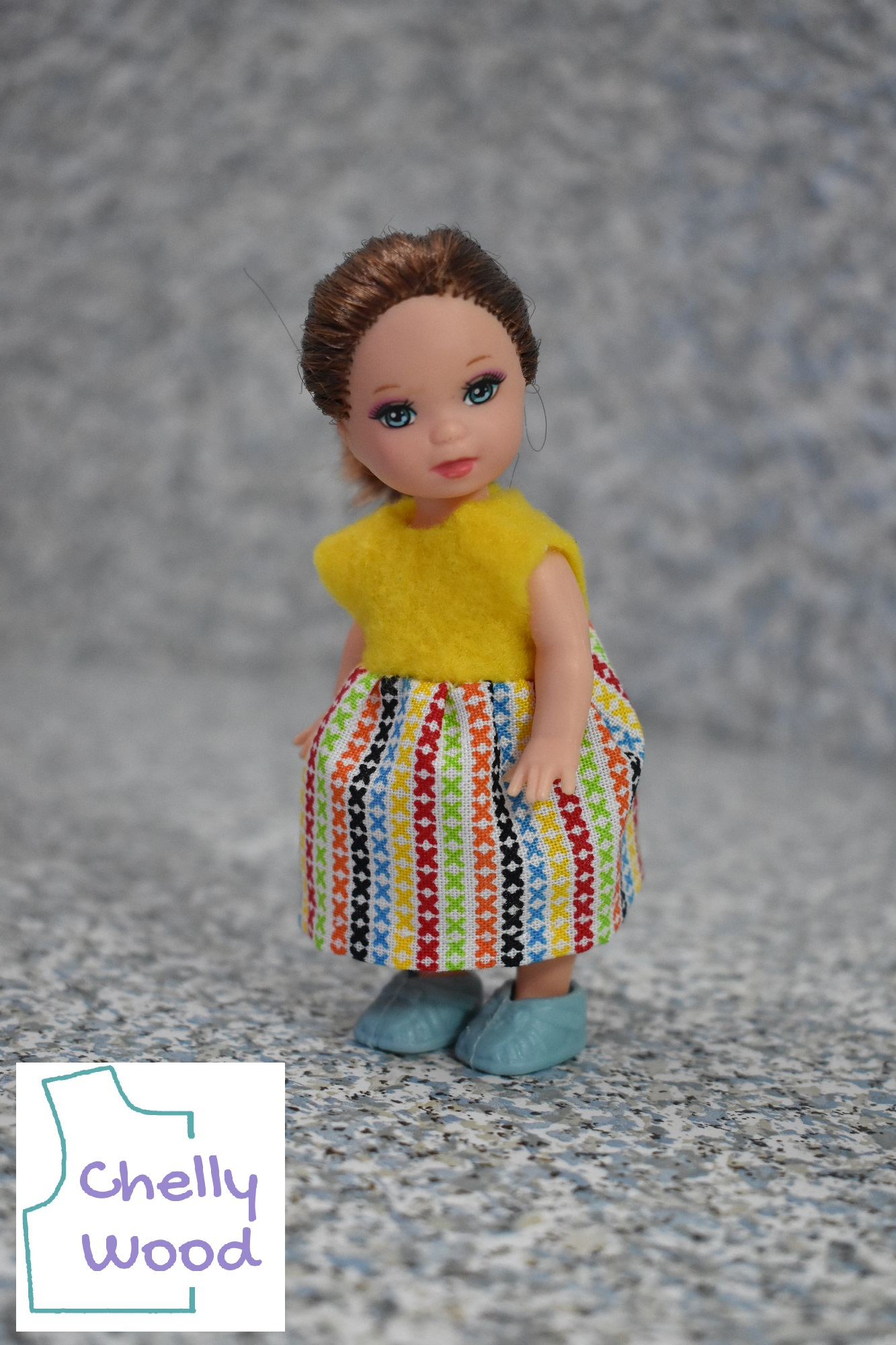 """The image shows a 4 inch (10 centimeter) Mattel Kelly doll wearing a handmade dress and standing on what appears to be a miniature concreted floor. She has auburn hair and light green eyes. Her dress is made of yellow felt on top and multi-colored cotton in the skirt area. The skirt's multi-colored fabric print has teeny-tiny X's that make a sort of striped pattern of colors: green, then orange, then black, then blue, then yellow, then red, then back to green. The doll wears tiny hard plastic blue shoes on her itty bitty feet. We also see the watermark that says, """"Chelly Wood"""" inside the shape of a bodice pattern."""