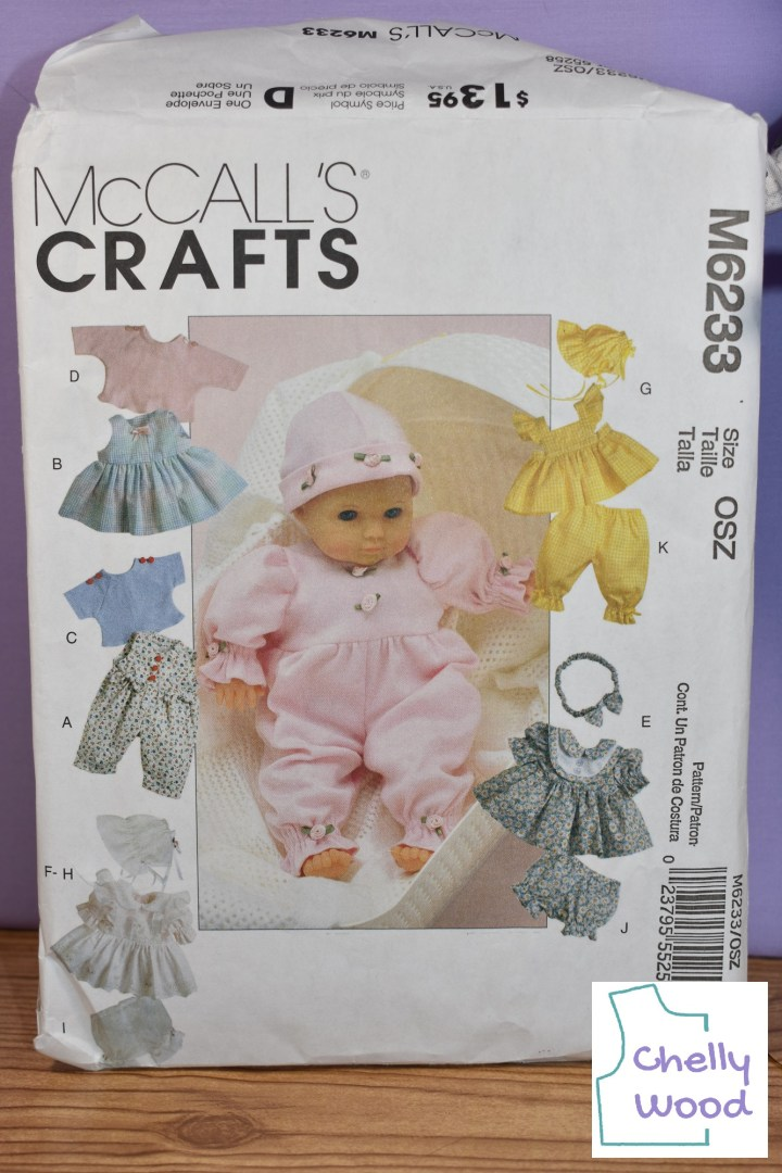"""Here we see a close-up image of the McCall's CRAFTS M6233 Baby Doll Clothes pattern. The baby doll clothes include the following: a long-sleeved T-shirt with raglan sleeves, a short-sleeved T-shirt with raglan sleeves, a sundress, a jumpsuit, a bonnet, a ruffled dress, a pair of bloomers with a pinafore dress, and a floral dress with a layered collar and shorter bloomers. The doll in the center wears a long-sleeved version of the jumpsuit with ruffled along the edges of the sleeves, ruffles along the bottom of each pant leg, and a stocking cap. If you'd like to learn more about this pattern and where to find it online, please go to ChellyWood.com and click on """"Old Patterns from Chelly's Collection"""" in the categories."""