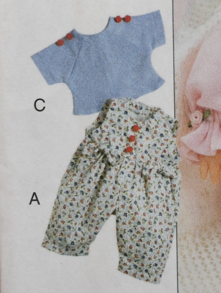 In the image, we see a pretty floral sleeveless jumpsuit with floral ties where the bodice joins the pants. It has little red buttons down the front. Behind it and turned slightly at an angle so we can see almost the whole garment, is a pale blue raglan-sleeved T-shirt with red buttons across the shoulders. Because of the blue flowers in the pants suit, and due to the use of identical decorative buttons, it seems likely that the designer intended for this T-shirt and this jumpsuit the be worn together.