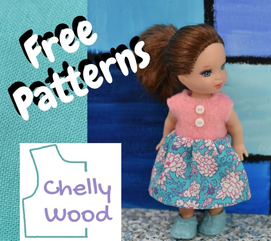 The image shows a tiny Kelly doll wearing a miniature doll dress made of pink felt, blue floral print cotton, and two tiny plastic buttons. If you'd like to make this little dress for your Kelly doll or other 4 inch dolls, please navigate over to ChellyWood.com where the patterns are available for free as a PDF downloadable free sewing pattern.