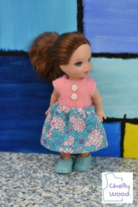 In this image, a tiny little Kelly doll with blue eyes and auburn hair models a handmade doll dress made of pink felt and blue, pink, and white floral print cotton fabric. Down the front of the pink felt bodice, there are two tiny white plastic buttons that really accentuate the white flowers on the blue background of the dress's skirt. The doll also wears tiny powder blue shoes. She stands on a concrete floor in front of a large stained glass window or a painting that's supposed to look like stained glass. The watermark reminds us that the free printable PDF doll clothes patterns for making this miniature doll dress with buttons comes from ChellyWood.com