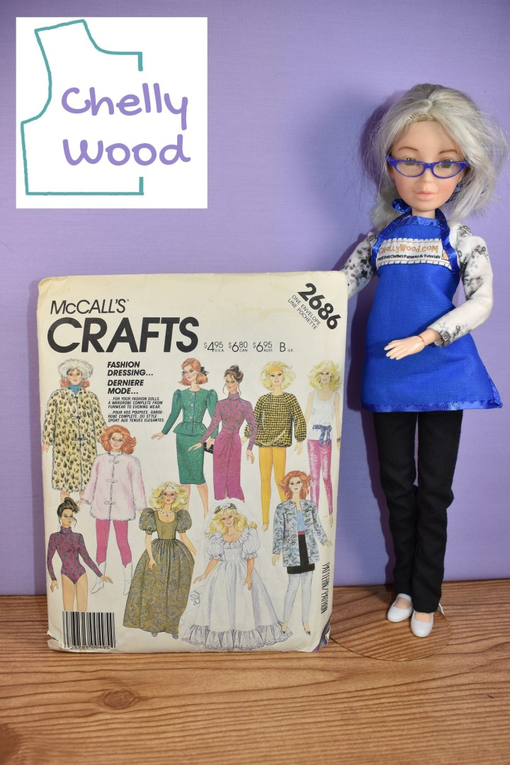 The Chelly Wood doll stands to the right of McCall's Craft Pattern 2686, which offers 10 different doll clothes outfit patterns to fit Barbie and similar sized fashion dolls. The watermark on the image reminds us that this photograph comes from ChellyWood dot com, a website that offers free printable sewing patterns for making doll clothes to fit dolls of many shapes and all different sizes. This particular illustration accompanies a website discussion about which fabrics are ideal for sewing doll coats for 11 inch fashion dolls like Barbies.