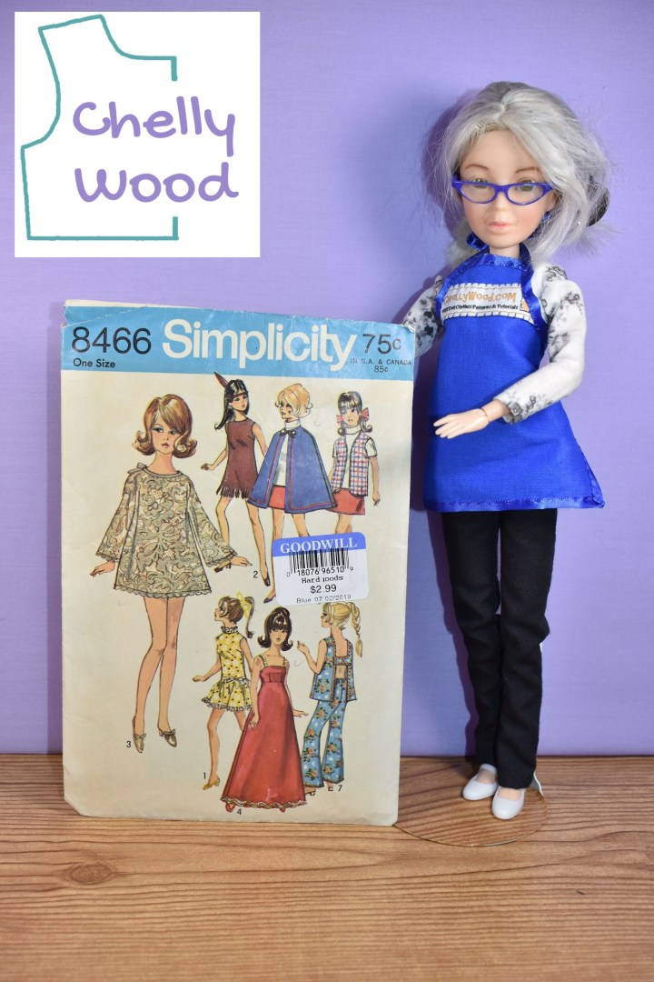 In this photograph, we see the Chelly Wood doll (a repainted Spin Master Liv doll that looks like the real doll clothing designer Chelly Wood) holding up vintage Simplicity doll clothes pattern number 8466, which was published in 1969. The pattern offers the following outfits to fit Barbie sized fashion dolls of the time: View 1: a sleeveless dress with high lace collar and a ruffle; view 2: a sleeveless dress with fringe at the bottom in imitation of a Native American style mini skirt; view 3: a bell sleeved mini skirt dress; view 4: a ball gown with empire waist and straps; view 5 a short sleeved turtle neck shirt with mini skirt and vest; view 6: the same mini skirt and short sleeved turtle neck are shown with a blue cape over the top; view 7: bell bottom pants with an elastic waist and a sleeveless shirt that has a buckle style open back.