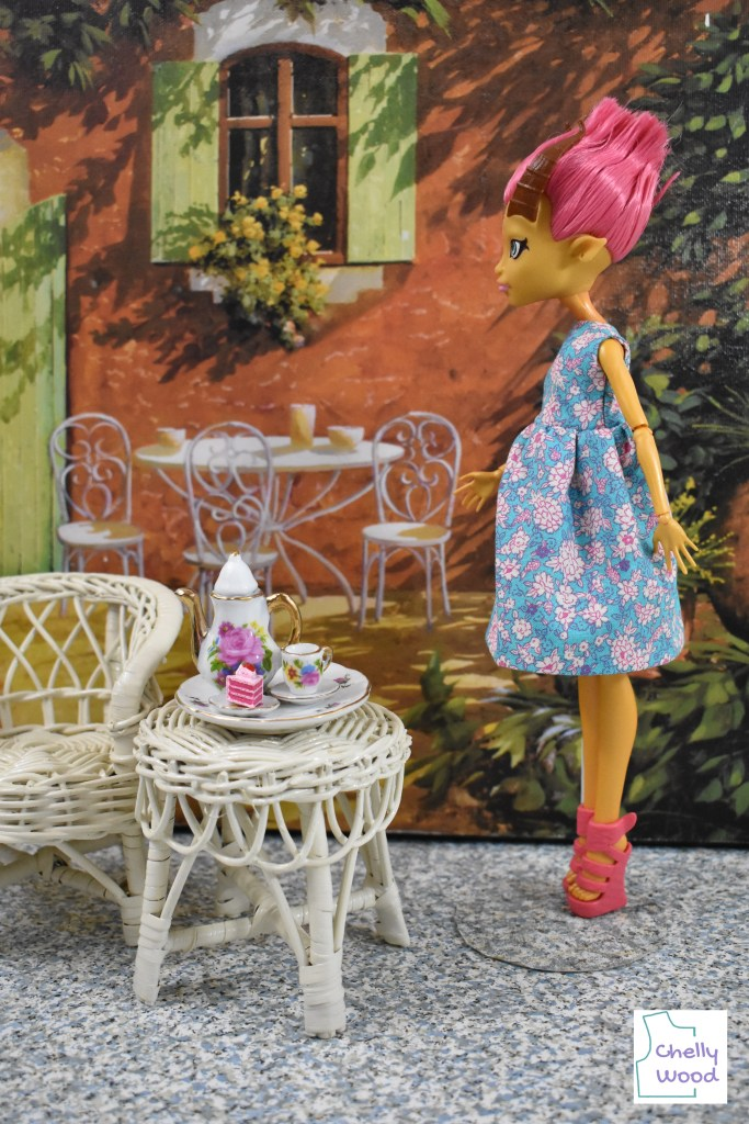 This photograph shows the Monster High doll called Gilda Goldstag wearing a handmade pink, white, and blue floral sleeveless dress. The skirt length is just below the knee of the doll. The doll stands in a diorama that looks a lot like an Italian restaurant. Beside her are a wicker chair and a wicker table. On the wicker table is a tea set and a slice of layer cake in shades of pink to match the doll's pink hair, pink shoes, and white flowers outlined in pink that appear as tiny printed motifs within the fabric of the dress. The photo is marked with the Chelly Wood logo, reminding you to visit ChellyWood.com for all your free printable PDF sewing patterns for making doll clothes to fit dolls of many shapes and all different sizes (including the free printable sewing pattern for making this sleeveless dress).